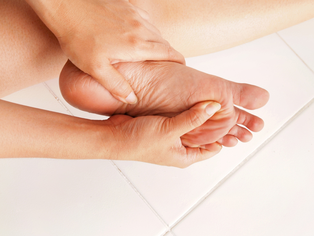 person with plantar fasciitis holding foot in pain