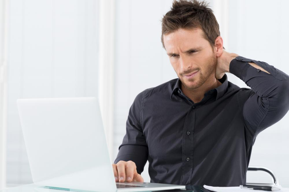 Man on the computer experiencing neck pain.